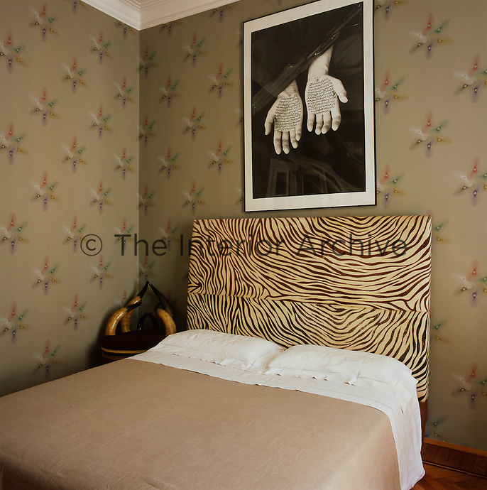 The bedroom has patterned wallpaper in muted colours and the double bed has a striking headboard with a Zebra skin pattern.