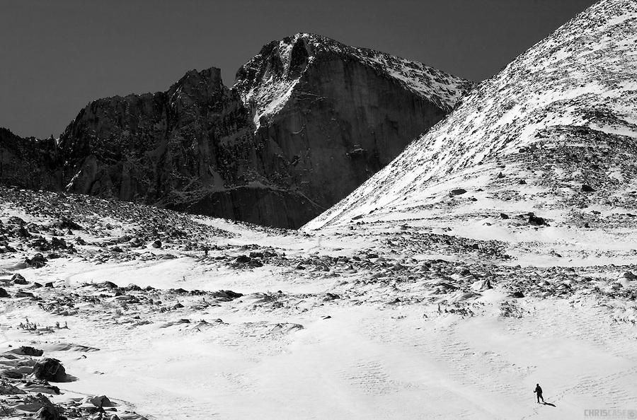 A lone figure crosses a snowy talus field below the looming face of The Diamond, Longs Peak, Colorado.