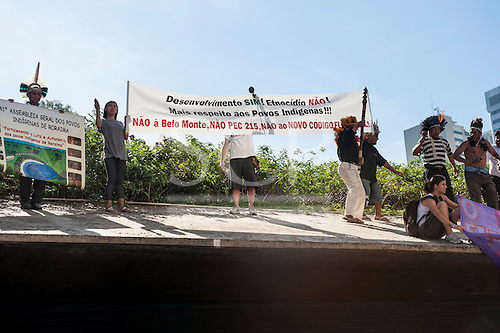 "Brazilian indigenous people protest with a banner announcing ""Development Yes! Ethnocide No! More Respect for Indigenous Peoples!! No to Belo Monte, No to PEC 215 [a law which would deny indigenous peoples some of the rights they have to claim ancestral land], No to the new Forest Code![ which will remove protection from large areas of the Amazon rain forest]"" on the roof of the entrance to BNDES, the Brazilian National Development Bank, following a march from the People's Summit at the United Nations Conference on Sustainable Development (Rio+20), Rio de Janeiro, Brazil, 18th June 2012. Photo © Sue Cunningham."