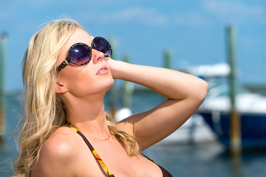 Beautiful blond woman in sunglasses and bikini relaxing and enjoying the summer sun at a tropical vacation with boats and marina behind.