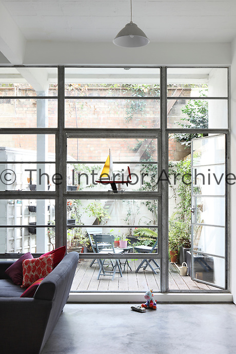 Industrial windows at one end of the open plan living area open onto a small patio garden