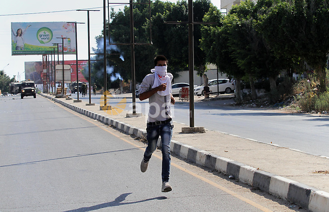 A Palestinian protester runs during clashes with Israeli troops following a protest in solidarity with Palestinian prisoners held in Israeli jails, at the Hawara checkpoint near the West Bank city of Nablus on Aug. 18, 2016. Photo by Nedal Eshtayah