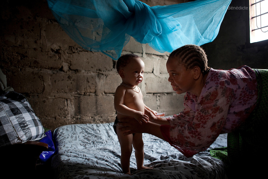 June 30, 2010 - Dar es Salaam, Tanzania - Fatima Husseni with her 11 months old albino daughter, Rairat Hamisi. Fatima Husseni and her husband Hamisi Husseni are not Albino, although four of their five children are albinos. Albinism is a recessive gene but when two carriers of the gene have a child it has a one in four chance of getting albinism. Tanzania is believed to have Africa' s largest population of albinos, a genetic condition caused by a lack of melanin in the skin, eyes and hair and has an incidence seven times higher than elsewhere in the world. Over the last three years people with albinism have been threatened by an alarming increase in the criminal trade of Albino body parts. At least 53 albinos have been killed since 2007, some as young as six months old. Many more have been attacked with machetes and their limbs stolen while they are still alive. Witch doctors tell their clients that the body parts will bring them luck in love, life and business. The belief that albino body parts have magical powers has driven thousands of Africa's albinos into hiding, fearful of losing their lives and limbs to unscrupulous dealers who can make up to US$75,000 selling a complete dismembered set. The killings have now spread to neighboring countries, like Kenya, Uganda and Burundi and an international market for albino body parts has been rumored to reach as far as West Africa. Photo credit: Benedicte Desrus