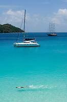 Seychelles, Island Praslin, Anse Lazio: sailing ship, catamaran, Anse Lazio Bay, man swimming<br />