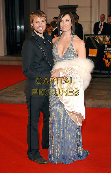 TONI COLLETTE & GUEST.Arriving at the 2007 Orange British Academy Film Awards (BAFTAs) at the Royal Opera House, London, England, 11th February 2007..full length grey gray silver beaded halterneck dress cream white fur collar coat jacket wrap cleavage black suit.CAP/ BEL.©Tom Belcher/Capital Pictures.