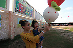 Palestinian girls carry candy cotton as they play at a park in Gaza city on August 18, 2019. Fayiz al-Wakeel, or 'the smile maker', developed his own candy floss machin to work by battery power to help him moving between vital districts in the Gaza city and make cotton candy with lovely shapes.. Photo by Mahmoud Ajjour