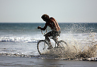"""Ranchito"" Ted (no last name given) skims through the surf in North PB on his bicycle, Tuesday, September 30, 2008."