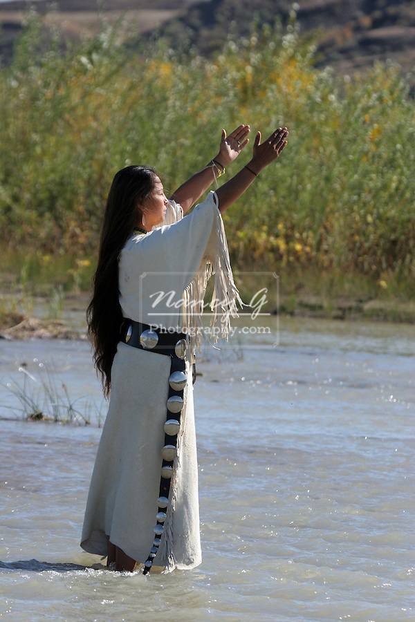 A Native American Indian women holding her hands up to the sun on a South Dakota Reservation