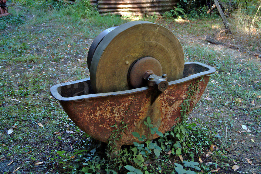 An antique grinding wheel powered by a belt drive and used to sharpen tools at an antique saw mill in Occidental California