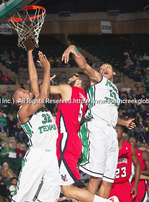 North Texas Mean Green forward Roger Franklin (32), North Texas Mean Green forward Tony Mitchell (13) and Louisiana Lafayette Ragin Cajuns forward J.J. Thomas (5) in action during the game between the Louisiana Lafayette Ragin Cajuns and the University of North Texas Mean Green at the North Texas Coliseum,the Super Pit, in Denton, Texas. Louisiana Lafayette defeats UNT 57 to 53.