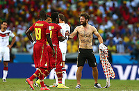A pitch invader with a long e-mail address written on his shirt shakes hands with Sulley Muntari of Ghana before being led off