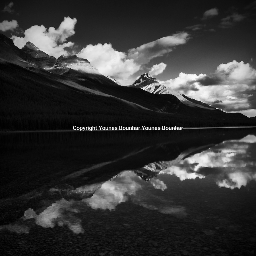 Moving clouds over waterfowl lake reflection in the late afternoon light, black and white