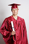 2013 Graduate in a red cap and gown with diploma