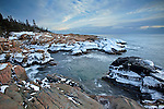 Waves swirl against the ice-covered granite rocks along the Schoodic Peninsula in Acadia National Park, Maine, USA