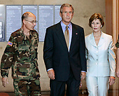 U.S. President George W. Bush (2L) and First Lady Laura Bush walk with Kenneth L. Farmer, Walter Reed's commander, after visiting injured U.S. soldiers at Walter Reed Army Medical Center in Washington, DC on Wednesday 5 October 2005. Bush present eight veterans with Purple Heart Medals. <br /> Credit: Matthew Cavanaugh / Pool via CNP