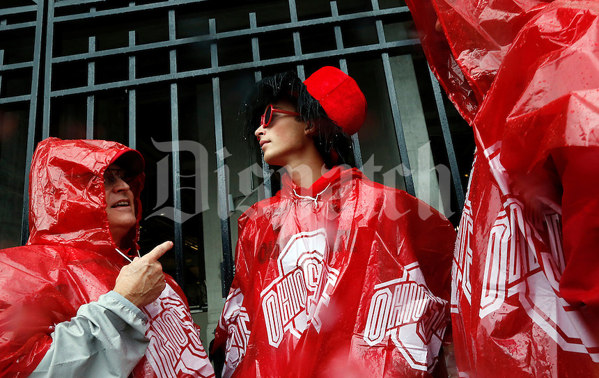 (from L) Richard Fires Sr., Zach Fires and Richard Fires Jr. (three generations- L grandfather, center grandson and r son) wait out the rain outside of the Ohio Stadium before the start of the NCAA football game between The Ohio State University and Florida A&M in Columbus, Ohio on September 21, 2013. (Columbus Dispatch photo by Brooke LaValley)