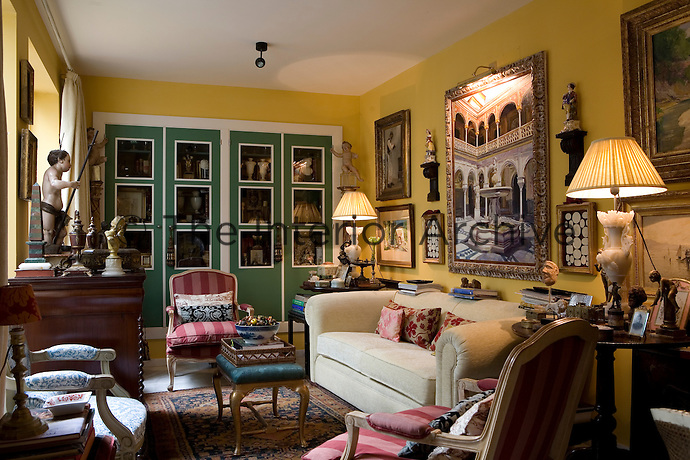 A traditional sitting room is decorated in a deep yellow and trimmed with dark green and bright white accent colours. The room features a cream sofa and antique chairs.