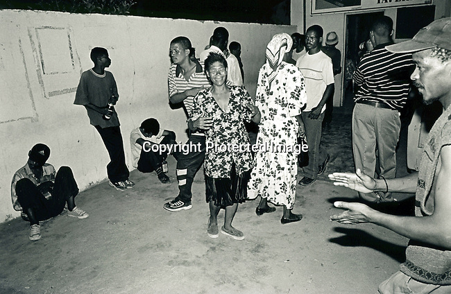 disiabu00038.Social Issues. Abuse. People dancing at a local Shebeen (illegal bar) on February 9, 2002 in Loisevale, Upington. These Shebeens are traditionally open 24 hours a day. Baby Thsepang was raped in October-2001 in Loisevale ner Upington, South Africa. Loisvale is a poor and destitute colored/black township where unemployment is very high and a high number of abuse and alcohol cases..©Per-Anders Pettersson/iAfrika Photos