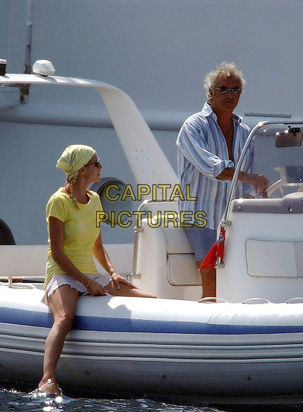 Heidi Klum & Flavio Briatore .On vacation on their yacht off Sardinia , Italy..July 9th, 2003.full length couple vacation holiday sun water blue stripe shirt bandana sitting yellow t-shirt profile side .CAP/PPG.©People Picture/Capital Pictures