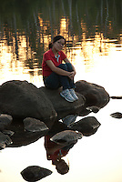 Woman sitting on rocks in lake at sunset, sunset reflecting on the water behind her.