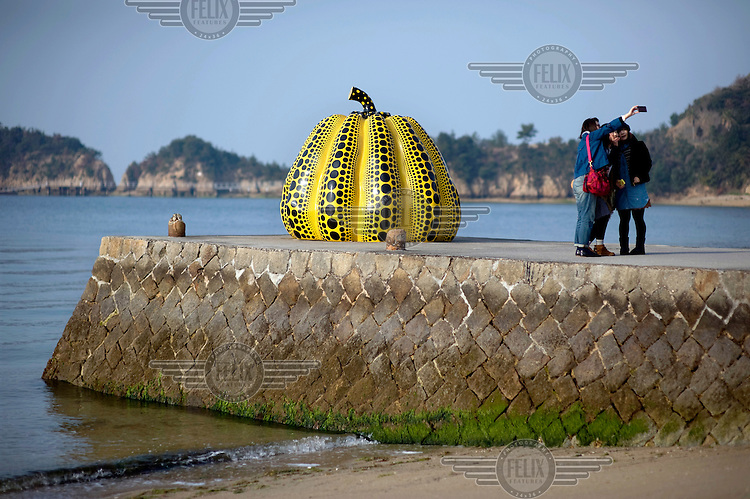 Visitors take a picture of themselves with an installation of a yellow pumpkin by Yayoi Kusama at the Benesse Art House on Naoshima Island. /Felix Features