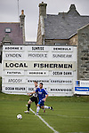 Players framed by an advertisement showing the names of local fishing boats at Bellslea Park, during Fraserburgh's Highland League fixture against visitors Strathspey Thistle (in blue). Nicknamed 'The Broch,' Fraserburgh have been members of the Highland League since 1921 having been formed 11 years earlier. The match ended in a 2-2 draw in front of a crowd of 302.