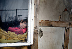 A Roma girl looks through the dirty window of her simple home, located under a bridge in Belgrade, Serbia.  The families that lived here, most of whom survive from recycling cardboard and other materials, were forcibly evicted in April 2012. Many, including this girl, were moved into metal shipping containers on the edge of Belgrade.