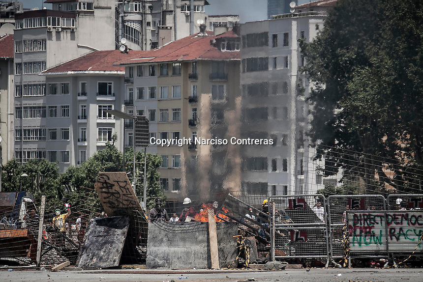 n this Tusday, Jun. 11, 2013 photo, protesters take cover behind a barricade during clashes at the streets of Taksim Square in Istanbul,Turkey. (Photo/Narciso Contreras).