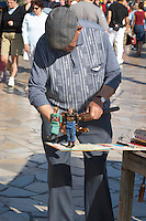 A street entertainer, old man showing to children two carved wooden dancing dolls Sanary Var Cote d'Azur France