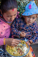 Nepal, Kathmandu.  Mother and Son Having Lunch.