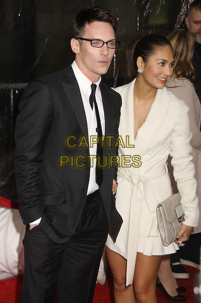 "JONATHAN RHYS MEYERS & REENA HAMMER .At the ""From Paris with Love"" New York Premiere held at the Ziegfeld Theatre, New York, NY, USA, 28th January 2010..half length suit hand in pocket white shirt girlfriend couple cream coat belted belt wrap clutch bag beige  glasses black tie  .CAP/ADM/AC.©Alex Cole/Admedia/Capital Pictures"