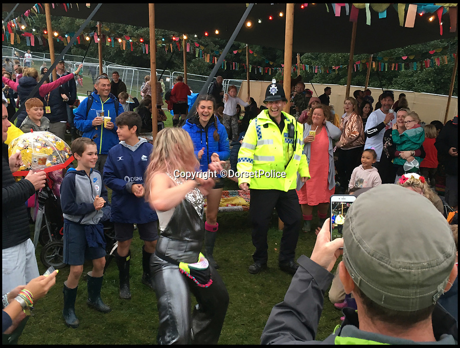 BNPS.co.uk (01202 558833)<br /> Pic: DorsetPolice/BNPS<br /> <br /> Bobby on the beat...<br /> <br /> Hilarious footage of a uniformed police officer 'dad dancing' at a music festival has been captured.<br /> <br /> Cheery special constable Jason Cox couldn't resist strutting his stuff when challenged to a dance off by revelers at Camp Bestival in Dorset. <br /> <br /> SC Cox can be seen throwing his arms into the air and jiggling along to the beat of hip hop hit Hey Ya! by Outkast. <br /> <br /> Dorset Police posted the video to social media, where it has been viewed over 25,000 times.