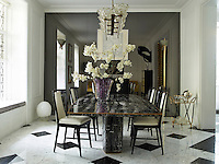The dining room has a smokey mirrored wall, which gives the room an impressive sense of space. The marble table and black lacquered dining chairs add glamour.