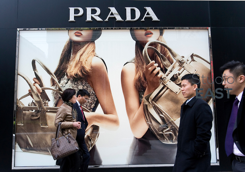 Middle-class white-collars walk pass a Prada giant advertisement in Shanghai, China, on April 13, 2010. Photo by Lucas Schifres/Pictobank