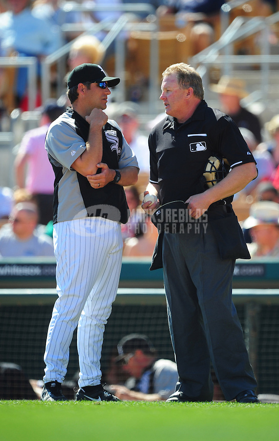 Mar. 14, 2012; Phoenix, AZ, USA; Chicago White Sox manager Robin Ventura (left) talks with umpire Bill Miller in the fifth inning against the Anaheim Angels at The Ballpark at Camelback Ranch. Mandatory Credit: Mark J. Rebilas-