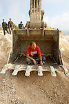 An international activist sits in the bucket of an bulldozer as Israeli border police arrive during a non-violent action to prevent the construction of Israel's controversial West Bank barrier in the village of Al Walaja near Bethlehem on 09-06-2010.