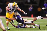 Sept. 5, 2009; Seattle, WA, USA; LSU Tigers tight end (18) Richard Dickson is tackled by Washington Huskies linebacker (22) E.J. Savannah at Husky Stadium. LSU defeated Washington 31-23. Mandatory Credit: Mark J. Rebilas-
