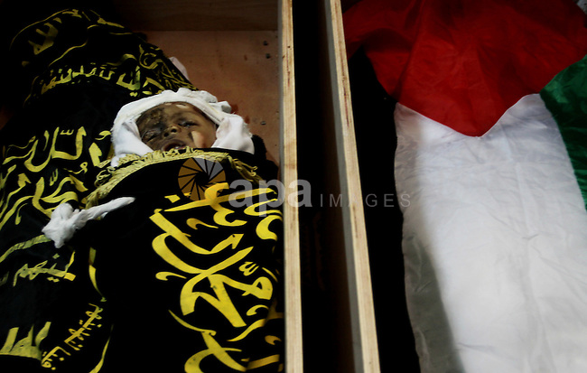 The bodies of Moataz Qreqa, a commander of Islamic Jihad's Al-Quds Brigade, his five-year-old son Islam and his brother Munzer lie in coffins during their funeral in Gaza City on August 20, 2011 after all three were killed when Israeli planes launched air strikes in Gaza in retaliation for suspected Islamist militants killing eight Israelis near the Egyptian border. Phot by Naaman Omar
