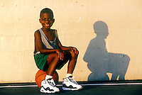 Smiling boy sits on his basketball.