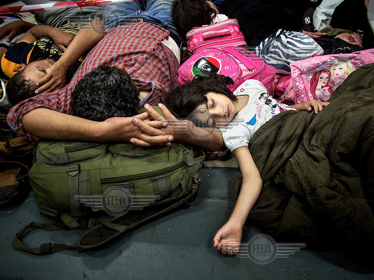 A young Syrian girl, who has travelled with her school bag, sleeps on her father's arm in the hold on board the Italian navy ship San Giorgio. With summer at its peak and the waves at their calmest, Italy's Mare Nostrum 'Rescue at Sea' operation has been inundated with arrivals of asylum seekers, mostly journeying from the coast of Libya. At least 5,000 were rescued at sea over the course of just 48 hours between 28-29 June 2014. Since the operation started, in October 2014, 73,686 people have been rescued while in distress at sea. Considered EU's largest such mission to date, Italy's decision to launch Mare Nostrum was a direct response to the more than 350 lives lost during twin shipwrecks off the coast of Lampedusa in October 2013.