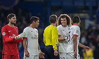 David Luiz of Paris Saint-Germain & teammates gather around Referee Felix Brych (GER) during the UEFA Champions League Round of 16 2nd leg match between Chelsea and PSG at Stamford Bridge, London, England on 9 March 2016. Photo by Andy Rowland.