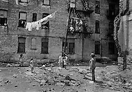 August 1971, Brooklyn, Bedford-Stuyvesant, NYC, NY. The long, hot summer of August 1971 exacerbated tensions in the black ghetto of Bronx. Poor housing, poverty, unemployment and crime did not facilitate the poor inhabitants during the heatwave. Children play in debris-strewn backyards behind a public housing block.