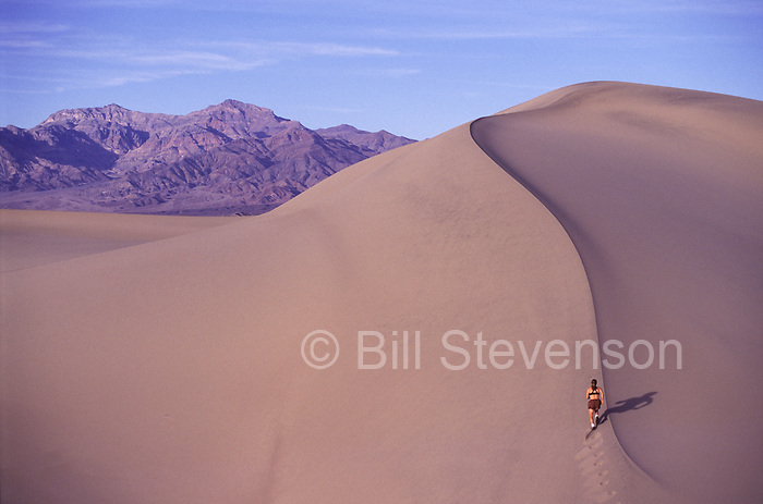 A picture of a woman running on a sand dune in Death Valley National Park, California