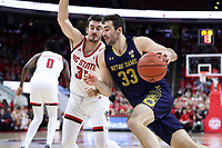 RALEIGH, NC - JANUARY 9: John Mooney #33 of the University of Notre Dame drives past Pat Andree #31 of North Carolina State University during a game between Notre Dame and NC State at PNC Arena on January 9, 2020 in Raleigh, North Carolina.