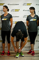 "Olympic medalist Michael Phelps ties his shoes next to his sisters  Whitney (L) and Hilary while they attend a event called ""Official Training Restaurant of the Phelps Family"" to support his sister Whitney as she runs the ING New York City Marathon on November 4.  the event was organized by the food company ""Subway"" in New York, United States. 15/10/2012. Photo by VIEWpress."