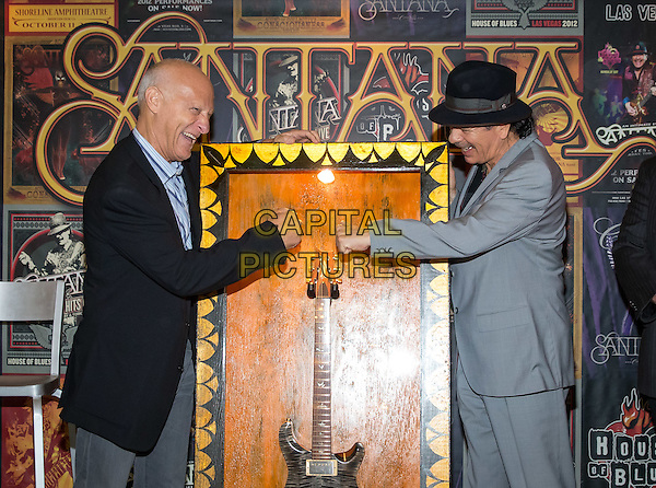 LAS VEGAS, NV - November 3: ***HOUSE COVERAGE*** <br /> Ron Bension, President, House of Blues Entertainment and Carlos Santana pictured as House of Blues executives honor Santana with the a commemorative display marking the sale of his 100,000th ticket to An Intimate Evening with Santana: Greatest Hits Live at House of Blues Las Vegas at Mandalay Bay Resort in Las Vegas, NV on November 3, 2015. <br /> CAP/MPI/EKP<br /> &copy;EKP/MPI/Capital Pictures