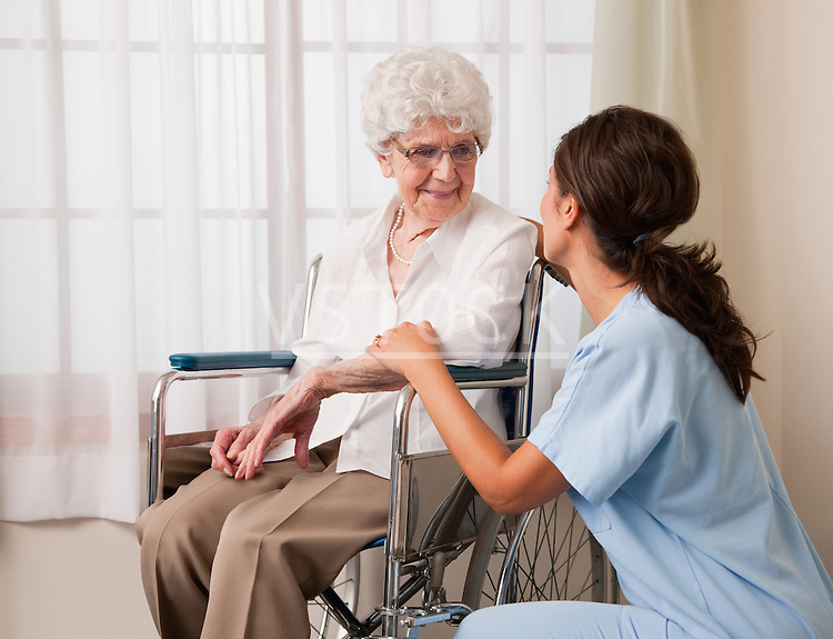 USA, Illinois, Metamora, Female nurse talking to senior woman on wheelchair