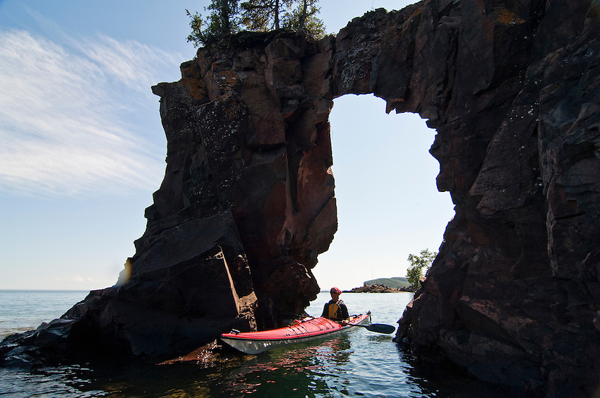 A sea kayaker explores a sea arch on Lake Superior at Tettegouche State Park on Minnesota's North Shore.