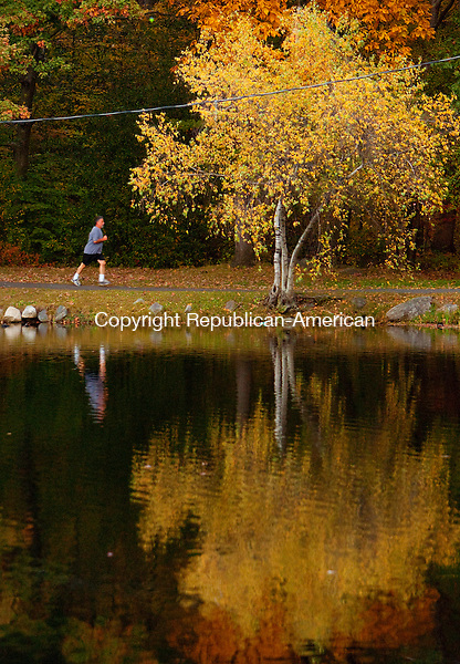 WATERBURY, CT, 18 OCTOBER 2010-101810JS05-Surrounded by the changing leaves and the colors of autumn, a runner makes his way around Upper Fulton Park Pond white jogging in Fulton Park in Waterbury on Monday. <br />  Jim Shannon Republican-American