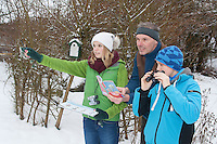 "Vogelbeobachtung im winterlichen Garten bei Schnee, Familie beim Vögel gucken, Fernglas, ""NABU Aktion Stunde der Wintervögel"", family watching birds, bird watching in winter, garden, snow, binoculars"